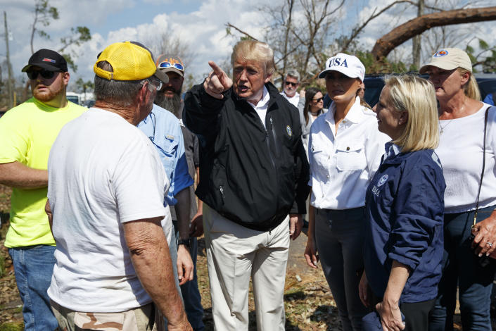 President Donald Trump and first lady Melania Trump talk to a Lynn Haven, Fla. resident, left, as Homeland Security Secretary Kirstjen Nielsen, second from right, and Margo Anderson, Mayor of Lynn Haven, Fla., right, look on, as they tour a neighborhood affected by Hurricane Michael, Monday, Oct. 15, 2018, in Lynn Haven, Fla. (AP Photo/Evan Vucci)