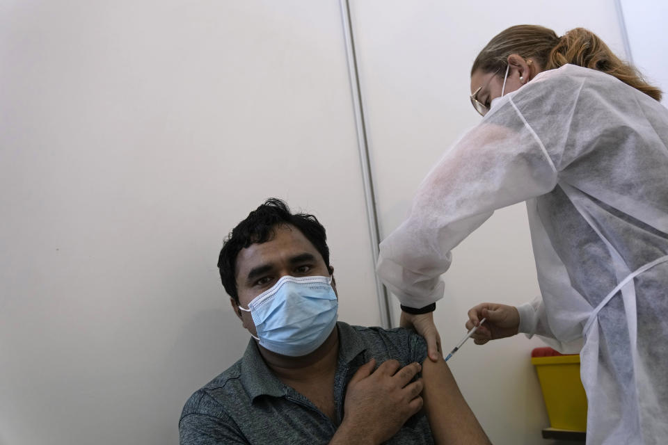 A military nurse administers a dose of the Pfizer coronavirus vaccine at a vaccination center in Lisbon, Tuesday, Sept. 21, 2021. As Portugal nears its goal of fully vaccinating 85% of the population against COVID-19 in nine months, other countries want to know how it was able to accomplish the feat. A lot of the credit is going to Rear Adm. Henrique Gouveia e Melo. (AP Photo/Armando Franca)