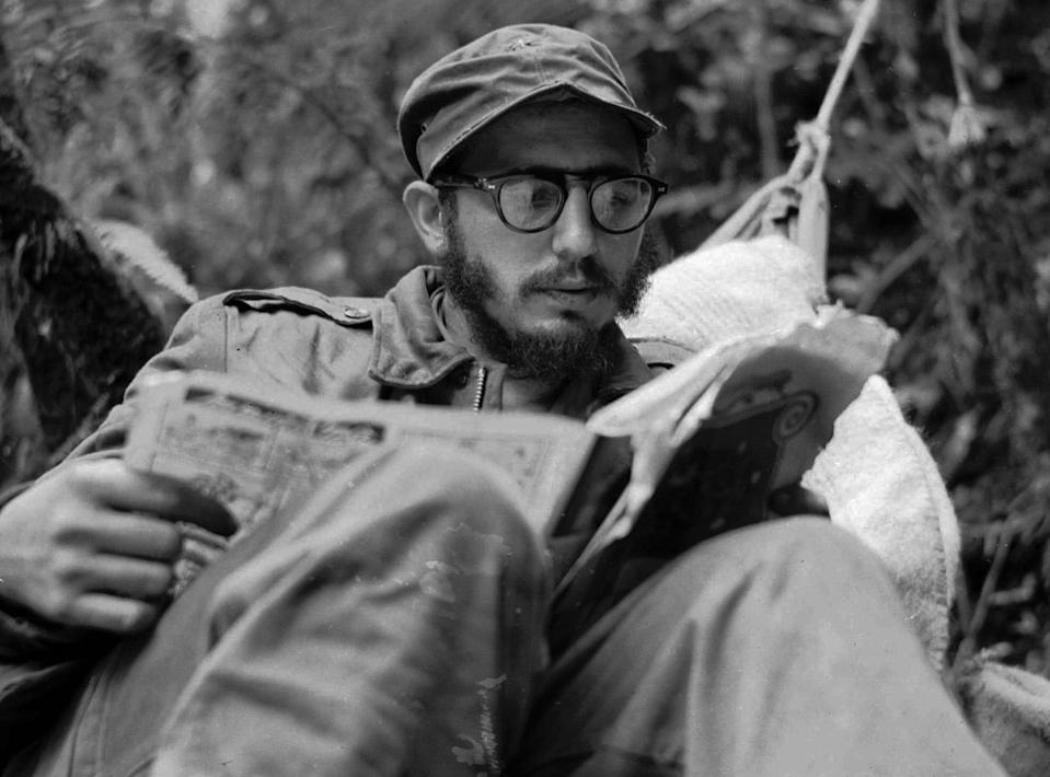 <p>Cuban guerrilla leader Fidel Castro does some reading while at his rebel base in Cuba's Sierra Maestra mountains in this 1957 photo. (AP Photo/Andrew St. George) </p>