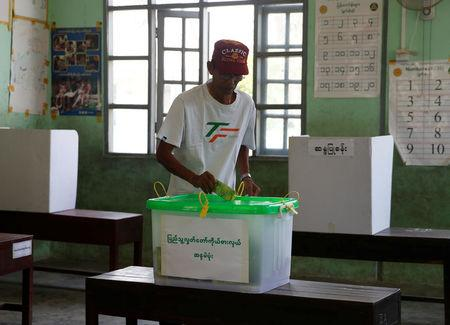 A man puts his ballot into a ballot box at a polling station as he vote during by-elections in Yangon