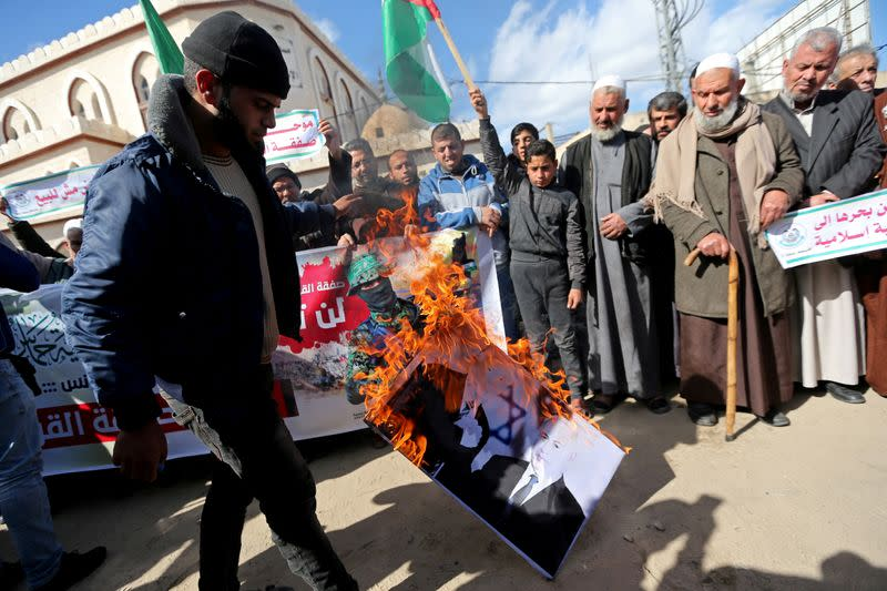 FILE PHOTO: A Palestinian demonstrator burns a picture depicting U.S. President Donald Trump and Israeli Prime Minister Benjamin Netanyahu, during a protest against Trump's Middle East peace plan, in the southern Gaza Strip