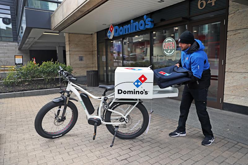 BOSTON, MA - MARCH 25: Javanshir Hajizada gets ready for a bicycle delivery for Domino's Pizza, which is hiring drivers, on March 25, 2020 in Boston. There have been an uptick in deliveries since many restaurants have completely closed to prevent the spread of coronavirus. (Photo by David L. Ryan/The Boston Globe via Getty Images)