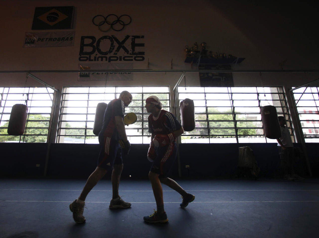 Great Britain's Olympic boxing coach Bob Dillon (L) practices with his boxer Amanda Coulson at the Santo Amaro club in Sao Paulo February 9, 2012. The women's boxing team from Great Britain is in Brazil to train with the Brazilian team between January 29 and February 12. According to the team, this exchange of experience with the South American boxers is part of their strategy for the London Olympics 2012, where women's boxing will be making its Olympic debut. Picture taken February 9, 2012.