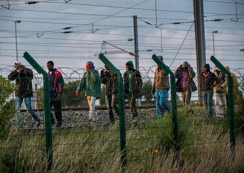 Migrants who successfully crossed the Eurotunnel terminal walk on the side of the railroad as they try to reach a shuttle to Great Britain, on July 28, 2015 in Frethun, northern France (AFP Photo/Philippe Huguen)