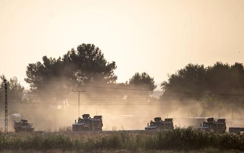 Turkish army vehicles drive towards the Syrian border near Akcakale  - Credit: BULENT KILIC/AFP