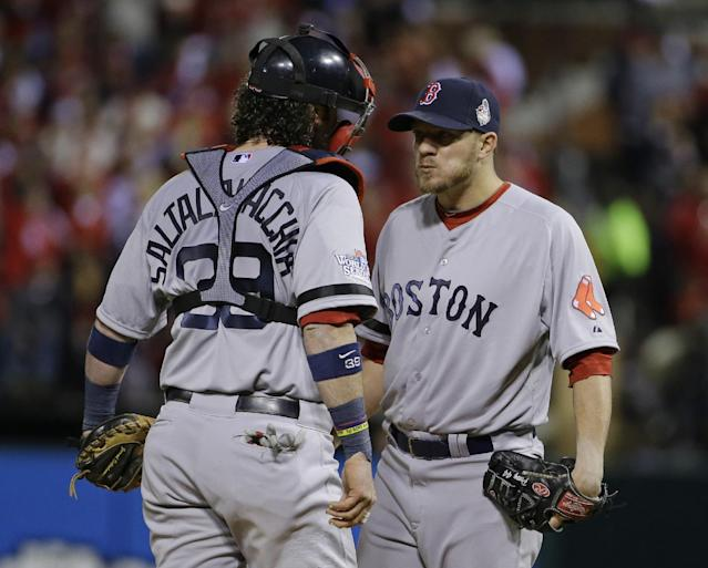 Boston Red Sox starting pitcher Jake Peavy, right, talks with catcher Jarrod Saltalamacchia during the first inning of Game 3 of baseball's World Series against the St. Louis Cardinals Saturday, Oct. 26, 2013, in St. Louis. (AP Photo/Matt Slocum)
