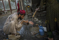 A displaced Afghan man drinks from a water tank at an internally displaced persons camp in Kabul, Afghanistan, Monday, Sept. 13, 2021. (AP Photo/Bernat Armangue)
