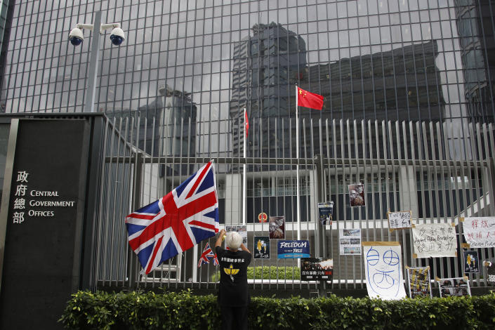 In this Thursday July 4, 2019, photo, Alexandra Wong, 63, a protester who's often seen raising the Union Jack at demonstrations and carried one into the legislative building on Monday night hangs posters outside the Central Government Office in Hong Kong. Two decades after Britain handed the city over to China, its colonial-era flag is still a potent symbol of the democratic values that many Hong Kong residents hold dear.(AP Photo/Andy Wong)