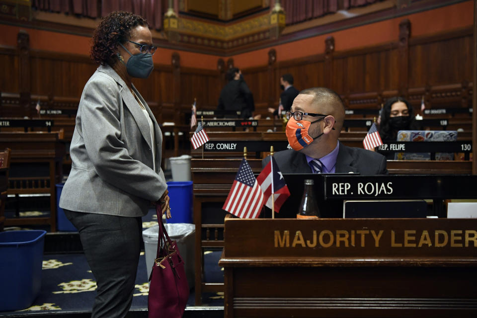 Connecticut House Majority Leader Jason Rojas, D-East Hartford, right, speaks with State Rep. Toni Walker, D-New Haven, left, during session at the State Capitol in Hartford, Conn., on Monday, April 19, 2021. In July 2020 after George Floyd was killed in Minneapolis, Black and Latino members of the Connecticut General Assembly worked to enact sweeping changes to policing in the state, and since, have continue to flex their collective muscles. (AP Photo/Jessica Hill)