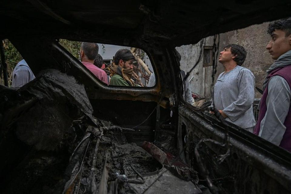 Afghan residents and family members of the victims gather next to a damaged vehicle (AFP/Getty)