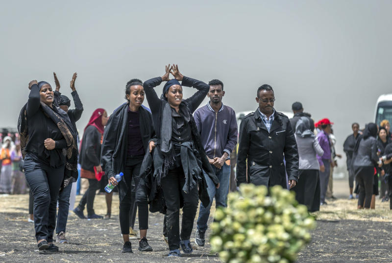 FILE - In this March 14, 2019 file photo, Ethiopian relatives of crash victims mourn at the scene where the Ethiopian Airlines Boeing 737 Max 8 crashed shortly after takeoff on Sunday killing all 157 on board, near Bishoftu, south-east of Addis Ababa, in Ethiopia. The investigation into the deadly plane crash in Ethiopia is continuing at a lab in France and the crash site. More details are emerging that suggest similarities between Sunday's crash of an Ethiopian Airlines Boeing 737 Max 8 jet and that of a Lion Air Max 8 Oct. 29 in Indonesia. (AP Photo/Mulugeta Ayene)