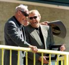 FILE - Former University of Oregon track coach Bill Bowerman shares a laugh with Nike CEO and Oregon alumni Phil Knight as Knight presents him with an award at Hayward Field during the Prefontaine Classic track meet in Eugene, Ore., in this May 30, 1999, file photo. Ever since track coach named Bill Bowerman tinkered with the idea of pouring rubber into his waffle iron to concoct a better shoe sole for running, Nike and track have grown together. (AP Photo/John Gress, File)