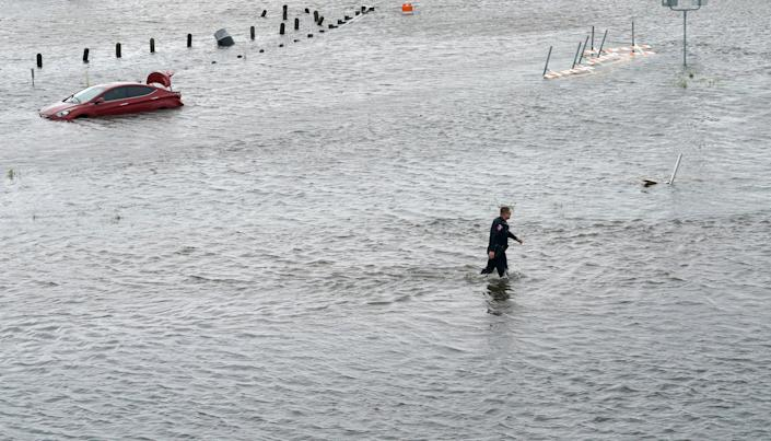 A police officer wades through floodwaters in Alvin, Texas, about 25 miles southeast of Houston. (Photo: Rick Wilking / Reuters)