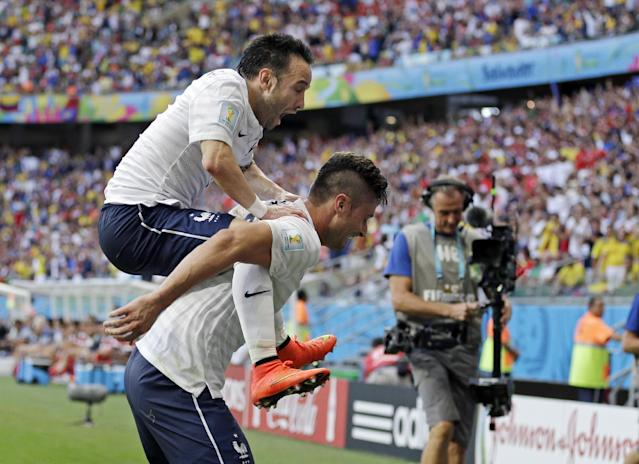 France's Mathieu Valbuena (8) jumps on Olivier Giroud's back after scoring his side's third goal during the group E World Cup soccer match between Switzerland and France at the Arena Fonte Nova in Salvador, Brazil, Friday, June 20, 2014. Giroud scored France's first goal. (AP Photo/Natacha Pisarenko)
