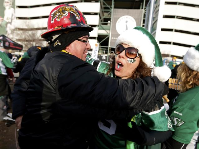 Hamilton Tiger Cat fan Joe Spilotro (L) embraces Saskatchewan Roughrider fan Carisa Polischuk outside the stadium prior to 101st Grey Cup championship football game in Regina, Saskatchewan November 24, 2013. REUTERS/Todd Korol (CANADA - Tags: SPORT FOOTBALL)