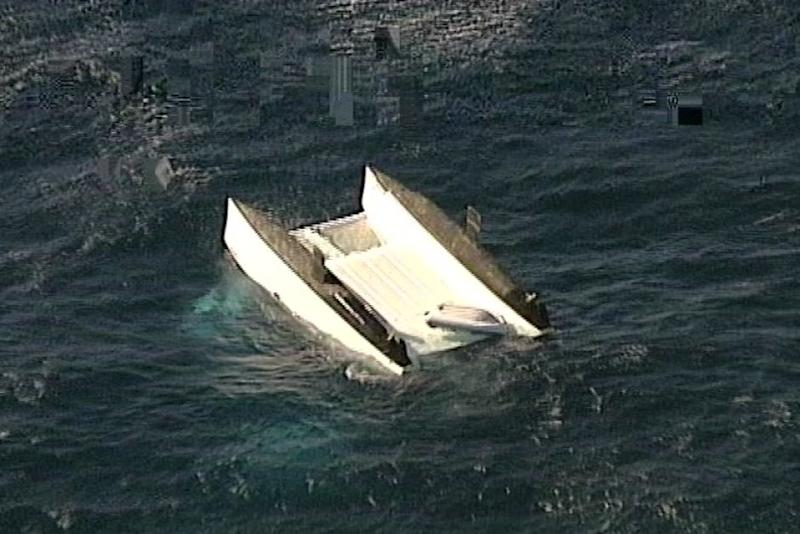 A catamaran is overturned in the water off Stockton Beach, Newcastle.