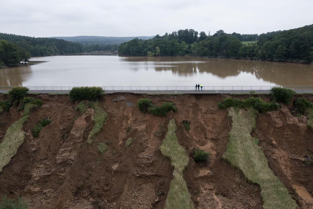 An aerial view shows people as they inspect the emptying of the damaged Steinbach hydrolic dam in Euskirchen, western Germany, on July 16, 2021, after heavy rain hit parts of the country, causing widespread flooding. - The death toll from devastating floods in Europe soared to at least 126 on July 16, most in western Germany where emergency responders were frantically searching for missing people. (Photo by SEBASTIEN BOZON / AFP) (Photo by SEBASTIEN BOZON/AFP via Getty Images)
