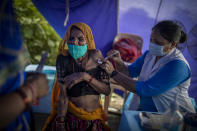 An elderly woman reacts as a health worker inoculates her during a special vaccination drive for homeless and migrant workers against COVID-19 in New Delhi, India, Wednesday, Sept. 15, 2021. (AP Photo/Altaf Qadri)