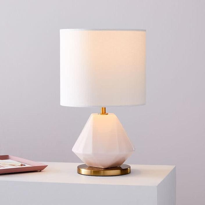 """If you're looking for something minimalist, this porcelain lamp just might catch your eye. This lamp features a faceted blush base, an """"Antique Brass"""" metal finish and a white linen shade. It is a plug-in, so you'll need a <a href=""""https://fave.co/32uZbGV"""" rel=""""nofollow noopener"""" target=""""_blank"""" data-ylk=""""slk:white LED bulb"""" class=""""link rapid-noclick-resp"""">white LED bulb</a>. <a href=""""https://fave.co/32u7F14"""" rel=""""nofollow noopener"""" target=""""_blank"""" data-ylk=""""slk:Find it for $63 at West Elm"""" class=""""link rapid-noclick-resp"""">Find it for $63 at West Elm</a>."""