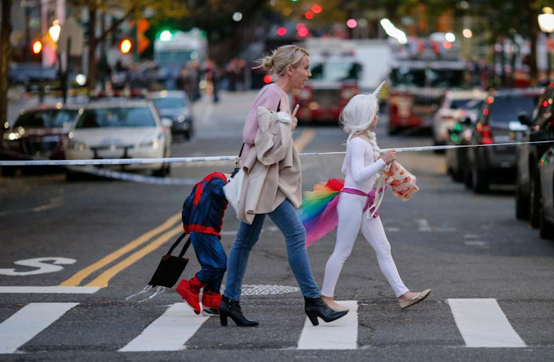 Kids in Halloween costumes cross the street near the scene where eight people were killed earlier in the day in a suspected terrorist attack in lower Manhattan.