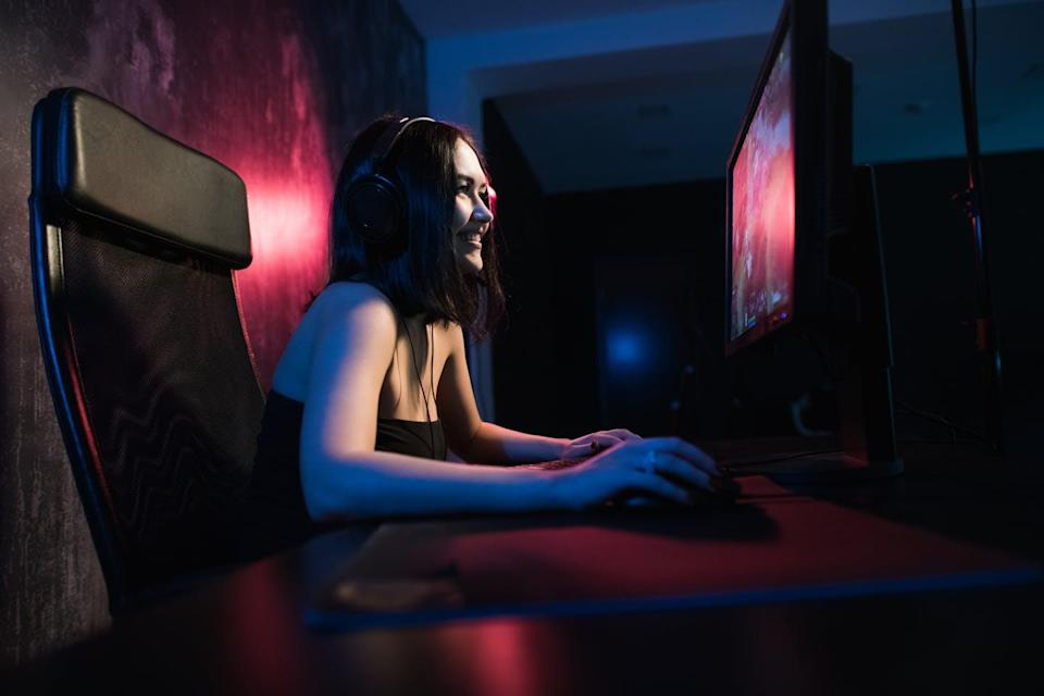 A young woman sits in front of a computer gaming set up.