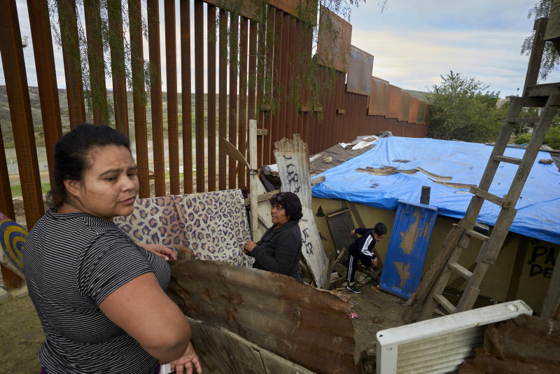 FILE - In this Jan. 16, 2019, file photo, Yuli Arias, left, stands near a newly-replaced section of the border wall as her mother, Esther Arias, center, stands in the family's house that was once threatened by construction along the border in Tijuana, Mexico. The Trump administration said Thursday, Feb. 7, 2019, it would waive environmental reviews to replace up to 14 miles (22.5 kilometers) of border barrier in San Diego, shielding itself from potentially crippling delays. (AP Photo/Gregory Bull, File)