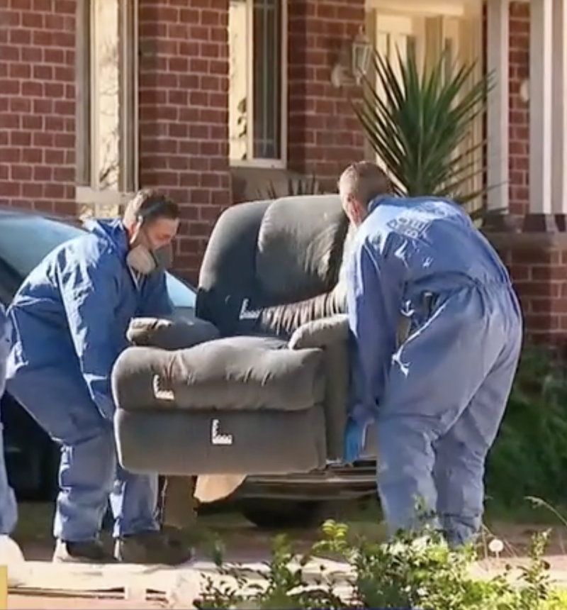 Photo shows two police officers removing a lounge chair from the home where the woman was found dead.