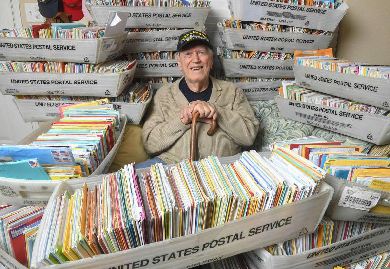 In this Tuesday, Jan. 8, 2019 photo, Duane Sherman, 96, poses at home with a small fraction of the 50,000 birthday cards he's received after his daughter's social media request for people to send him cards to cheer him up on his birthday went viral in Fullerton, Calif. (Kevin Sullivan/The Orange County Register via AP)