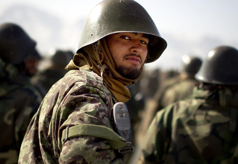 An Afghan National Army soldier looks on as he joins other comrades for a training session at the Kabul Military Training Center, KMTC, on the outskirts of Kabul, Afghanistan, Thursday, March 8, 2012. The Afghan National Army will be tasked with providing security throughout Afghanistan after the last international troops pull out in 2014. (AP Photo/Anja Niedringhaus)