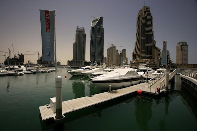 DUBAI, UNITED ARAB EMIRATES - MAY 01: Gleaming new boats rock gently in the newly established Dubai Marina while in the background construction proceeds at breakneck pace on May 1, 2006 in Dubai, United Arab Emirates. Dubai is a place where the line between the priveliged and the servile is often glaringly obvious. It is a society where the vast majority of people earn less than $200 a month and work in virtual servitude. Recently there was trouble in Dubai as migrant labourers protested at harsh working conditions and pay disputes. The labourers work long shifts on the 24 hour sites and the labour camps are often over 2 hours away. The workers typically work a 12 hour shift in tough conditions. The majority of labourers come to Dubai from India, Pakistan and Bangladesh. These workers operate in extreme temperatures in the desert climate, the majority earning under $200 a month. Many have to spend a third of that sum on food provided at the camps as part of their contract. Most sign recruitment contracts in their own countries which take them into debt for many years. Their passports are held by their employers once they reach the UAE and if the company owners abscond the workers are often abandoned without their documents or due payment. Over two thirds of the Dubai population is migrant labour with 1.1 million working in construction. Dubai is currently second only to Shanghai in terms of the scale of construction underway on a 24 hour basis. All this is woefully underscrutinised by the Ministry of Labour, there are currently only 80 government inspectors for over 200 000 construction companies. Recently there have been rumblings of discontent from the workers, with strikes at numerous sites over the non-payment of wages and harsh working conditions. In 2005, according to Human Rights Watch, there were 84 suicides by construction workers in Dubai. (Photo by Brent Stirton/Getty Images) *** Local Caption ***