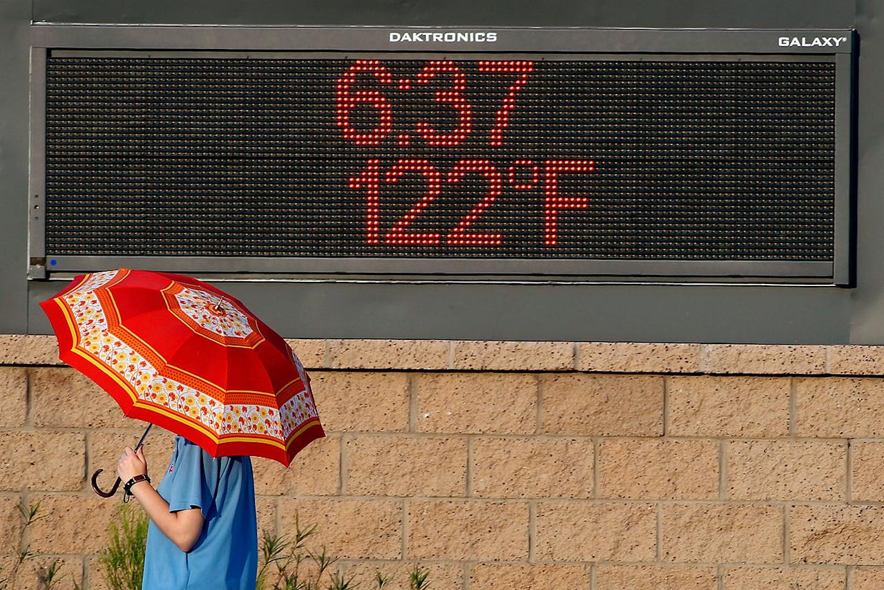 <p>A pedestrian uses an umbrella to get some relief from the sun as she walks past a sign displaying the temperature on June 20, 2017 in Phoenix, Arizona. Record temperatures of 118 to 120 degrees were expected on Tuesday for the Phoenix-metro area. (Ralph Freso/Getty Images) </p>