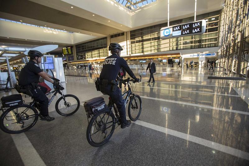 FILE - In this Nov. 2, 2013 file photo, airport police officers patrol the Tom Bradley International Terminal at the Los Angeles International Airport. Two armed police officers, not seen in this photo, assigned to guard a Los Angeles airport terminal where a gunman killed a screener in Nov. 2013, left for breaks without informing dispatchers as required minutes before the gunfire erupted. (AP Photo/Ringo H.W. Chiu, File)