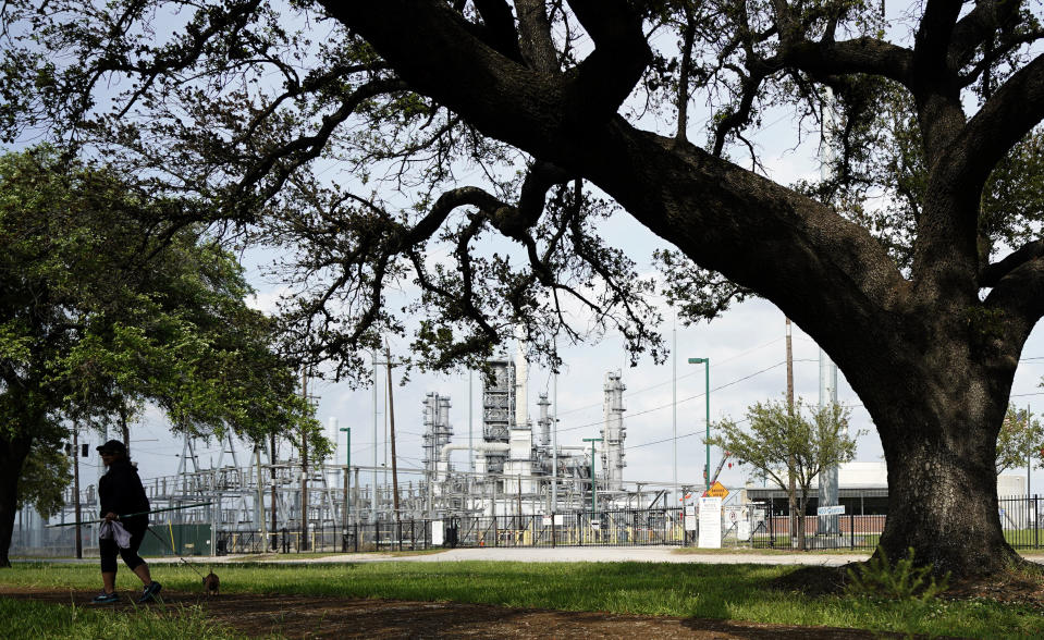 A woman walks her dog in Hartman Park next to the Valero Houston Refinery Monday, March 23, 2020, in Houston. (AP Photo/David J. Phillip)