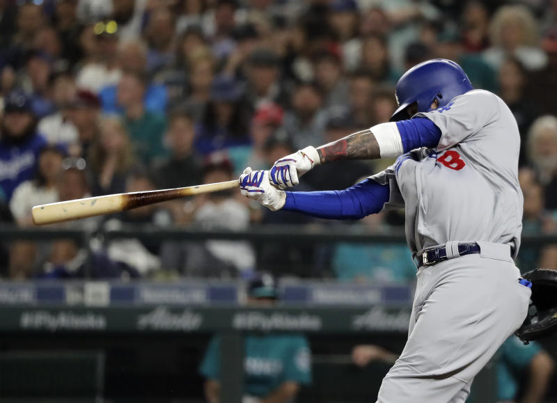 Los Angeles Dodgers' Manny Machado hits a two-run home run during the seventh inning of the team's baseball game against the Seattle Mariners, Friday, Aug. 17, 2018, in Seattle. It was Machado's second home run of the game. (AP Photo/Ted S. Warren)