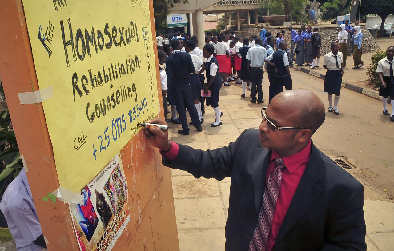 """Ugandan anti-gay activist Pastor Martin Ssempa posts up a public notice offering """"rehabilitation"""" for homosexuals at Uganda's National Theatre in Kampala, Uganda Tuesday, Feb. 25, 2014. U.S. Secretary of State John Kerry said Monday's signing of the anti-gay bill by President Yoweri Museveni, which punishes gay sex with up to life in jail, marked """"a tragic day for Uganda and for all who care about the cause of human rights"""" and warned that Washington could cut aid to the government of the East African nation. (AP Photo/Stephen Wandera)"""