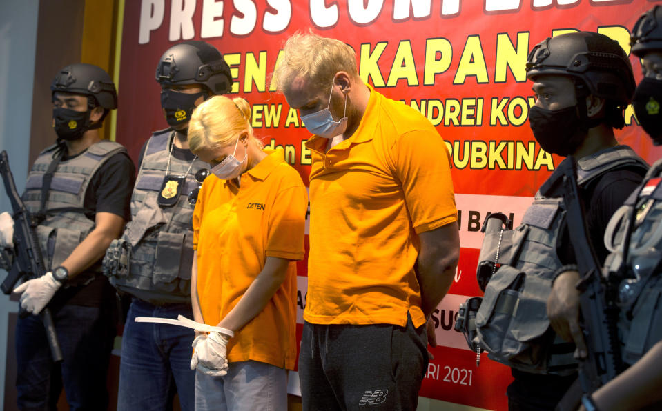 Police officers display Russian national Andrei Kovalenka, third from right, and his partner Ekaterina Trubkina, seeing during a press conference at the immigration office in Jimbaran, Bali, Indonesia, Wednesday, Feb. 24, 2021. Kovalenka, listed by the Interpol as a fugitive back home, was arrested on the Indonesian tourist island of Bali on Wednesday after 13 days on the run with his partner to avoid deportation. (AP Photo/Firdia Lisnawati)