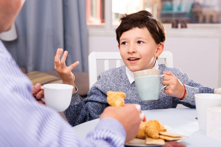 Boy talking to adult while drinking from a mug.