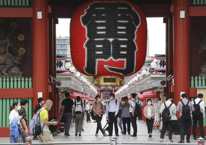 People wearing face masks to help protect against the spread of the coronavirus walk along the Asakusa area in Tokyo, Wednesday, June 30, 2021. (AP Photo/Koji Sasahara)
