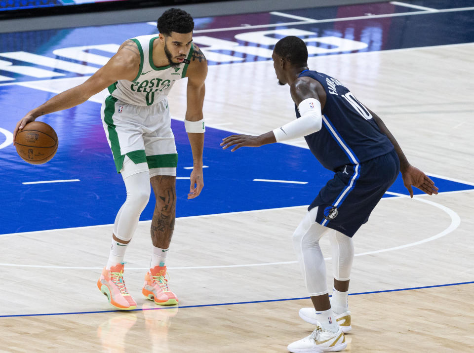 Boston Celtics forward Jayson Tatum (0) dribbles the ball as Dallas Mavericks forward Dorian Finney-Smith (10) defends during the first half of an NBA basketball game in Dallas, Tuesday, Feb. 23, 2021. (AP Photo/Sam Hodde)