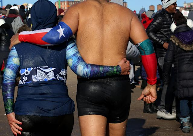<p>Polar Bear Club swimmers walk out of the Atlantic Ocean after making their annual icy plunge into it on New Year's Day, January 1, 2018, at Coney Island in the Brooklyn borough of New York City. (Photo: Yana Paskova/Getty Images) </p>