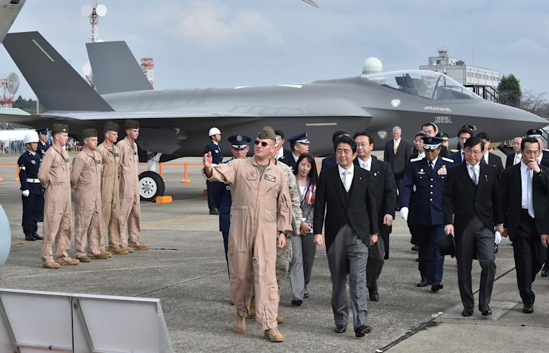 Japan's Prime Minister Shinzo Abe (C-R) inspects a mock-up F35A fighter (rear) as part of a static display during a review ceremony at the Japan Air Self-Defense Force's Hyakuri air base at Omitama, Ibaraki prefecture, on October 26, 2014 (AFP Photo/Kazuhiro Nogi)
