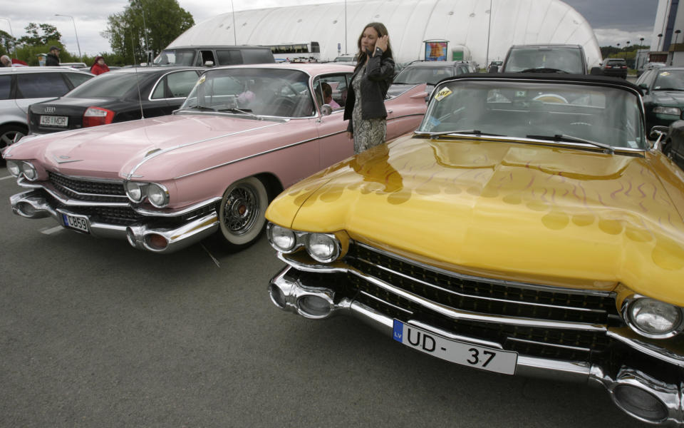 A woman poses between two Cadillac cars from the late1950s during an American car owners' meeting in Jurmala, about 20 km from capital Riga, May 23, 2009. REUTERS/Ints Kalnins (LATVIA SOCIETY TRANSPORT BUSINESS)