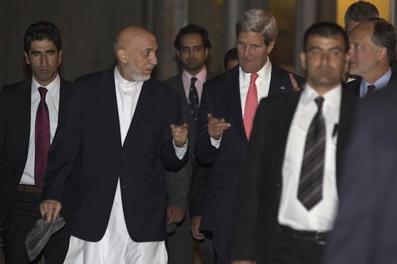 Afghan President Hamid Karzai, second from left, walks with U.S. Secretary of State John Kerry at the Presidential Palace during Kerry's unannounced stop to meet wit Karzai in Kabul, Afghanistan, on Friday, Oct. 11, 2013. (AP Photo/Jacquelyn Martin, Pool)