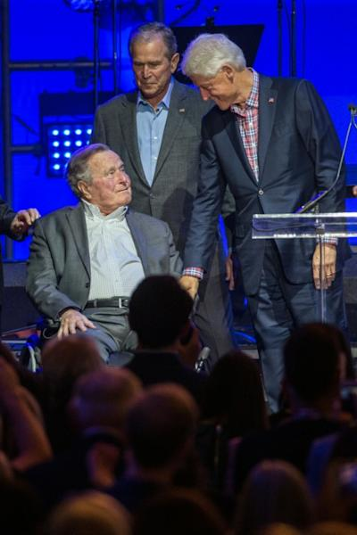 Former US President Bill Clinton, with President George W. Bush (C), greets President George H. W. Bush during the Hurricane Relief concert in College Station, Texas, on October 21, 2017