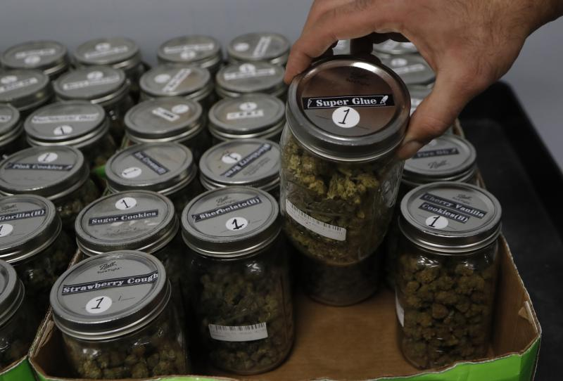 An attendant holds a mason jar of marijuana at a dispensary in Detroit, Michigan, where recreational marijuana has been legalized. Utah's law won't allow people with prescriptions to smoke the drug but they can obtain it in pill form or oils. (ASSOCIATED PRESS)