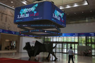 A huge screen shows the Korea Composite Stock Price Index (KOSPI) as a man, right, sits to check the body temperature of visitors at the Korea Exchange in Seoul, South Korea, Friday, July 2, 2021. Shares were mostly higher in Asia on Friday, though markets in Shanghai and Hong Kong declined a day after the Chinese Communist Party marked its centenary with tough talk by Chinese President Xi Jinping. (AP Photo/Lee Jin-man)