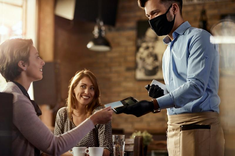 Young waiter wearing protective face mask while his guests are making contactless payment with credit card in a cafe.