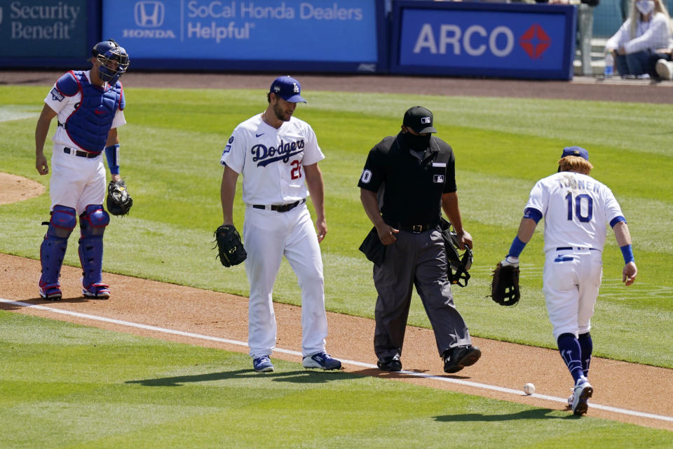 Los Angeles Dodgers catcher Austin Barnes, left, starting pitcher Clayton Kershaw, second from left, and third baseman Justin Turner, right, watch along with home plate umpire Adrian Johnson as a ball hit by Washington Nationals' Trea Turner rolls along the line and stays inbounds for a single during the sixth inning of a baseball game Sunday, April 11, 2021, in Los Angeles. (AP Photo/Mark J. Terrill)