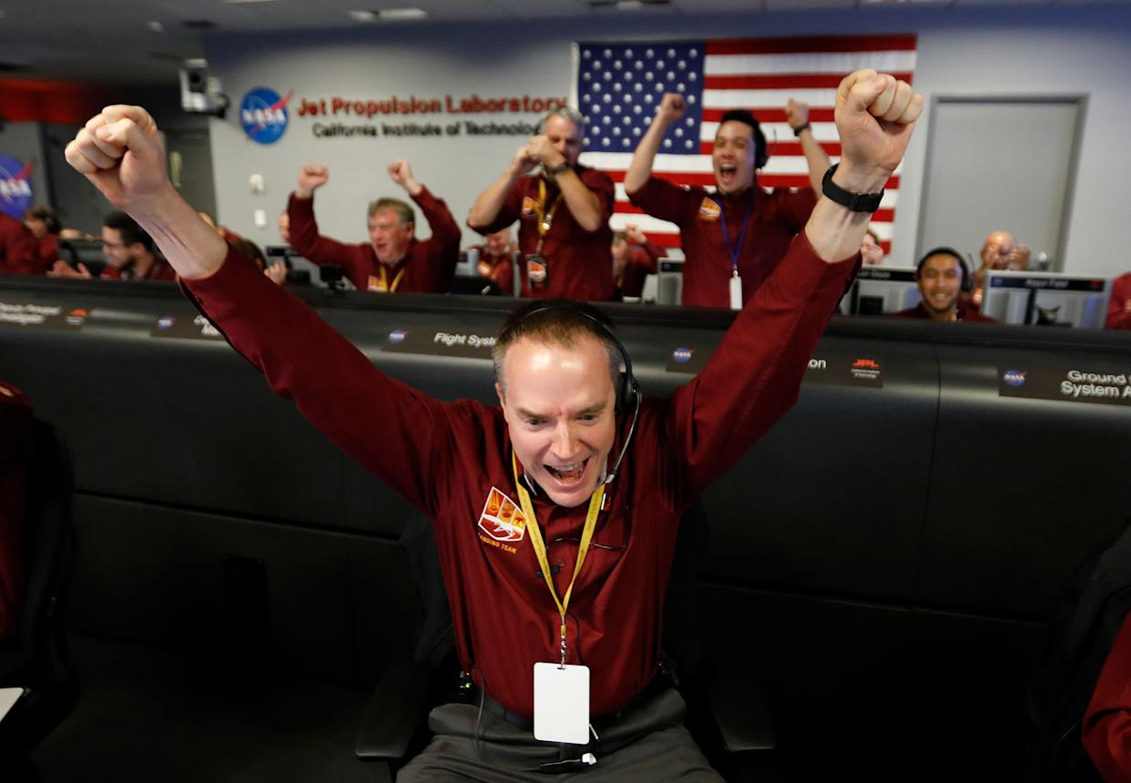 Engineer Kris Bruvold, bottom center, celebrates as the InSight lander touch downs on Mars. (Photo: ASSOCIATED PRESS)
