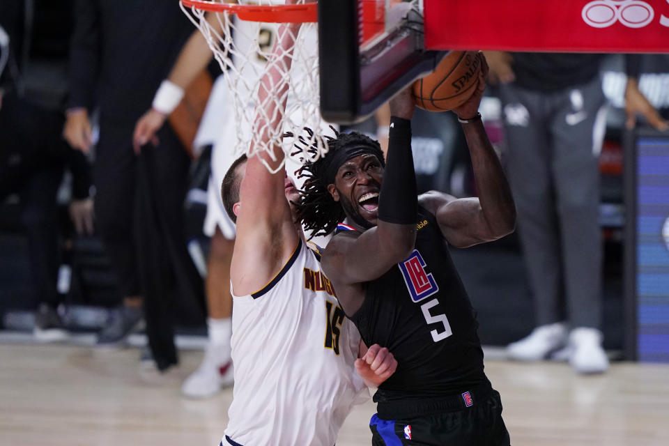 Los Angeles Clippers forward Montrezl Harrell (5) drives to the basket Denver Nuggets center Nikola Jokic (15) during the second half of an NBA conference semifinal playoff basketball game Tuesday, Sept. 15, 2020, in Lake Buena Vista, Fla. (AP Photo/Mark J. Terrill)